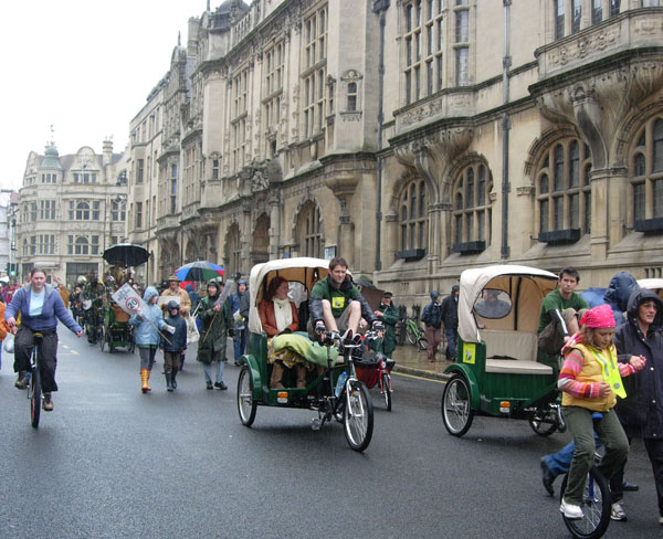 Rickshaws and unicycles pass the Town Hall